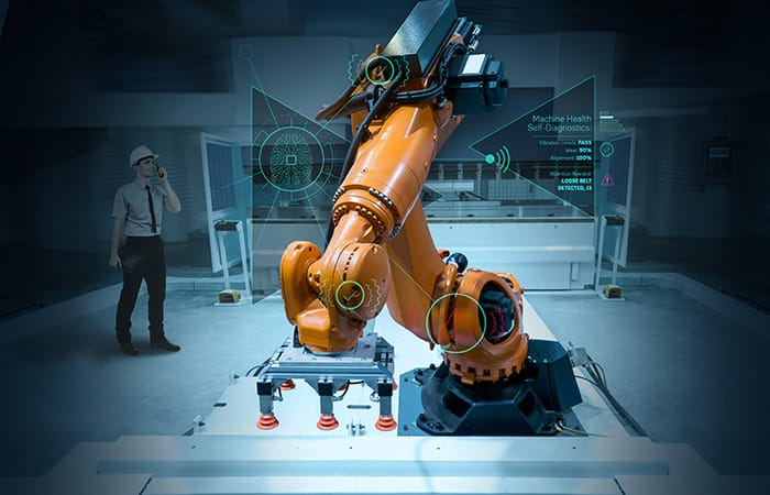 Orange automated robotic arms grabbing and lifting boxes of electronic appliances.