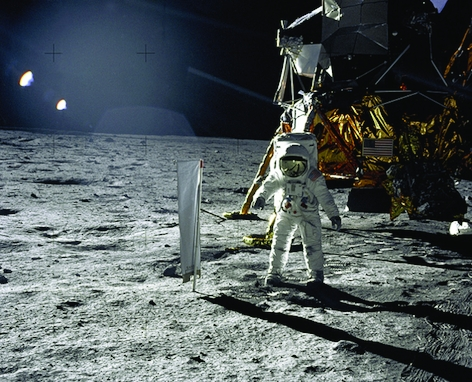 """Astronaut Edwin E. Aldrin, Jr., lunar Module pilot, is photographed during the Apollo 11 extravehicular activity (EVA) on the lunar surface. In the right background is the Lunar Module """"Eagle."""" On Aldrin's right is the Solar Wind Composition (SWC) experim"""