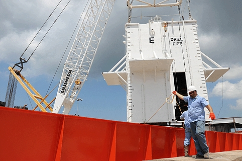 Crewmen aboard the motor vessel Joe Griffin guide a cofferdam onto the deck. The chamber is designed to contain the oil discharge before it reaches the surface.