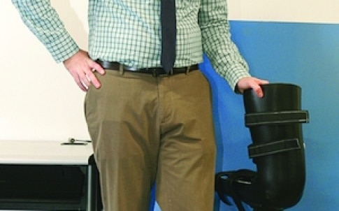 Dr Robert Gregg stands next to a robotic leg that was designed by UTDesign students and is similar to the one reported in his research