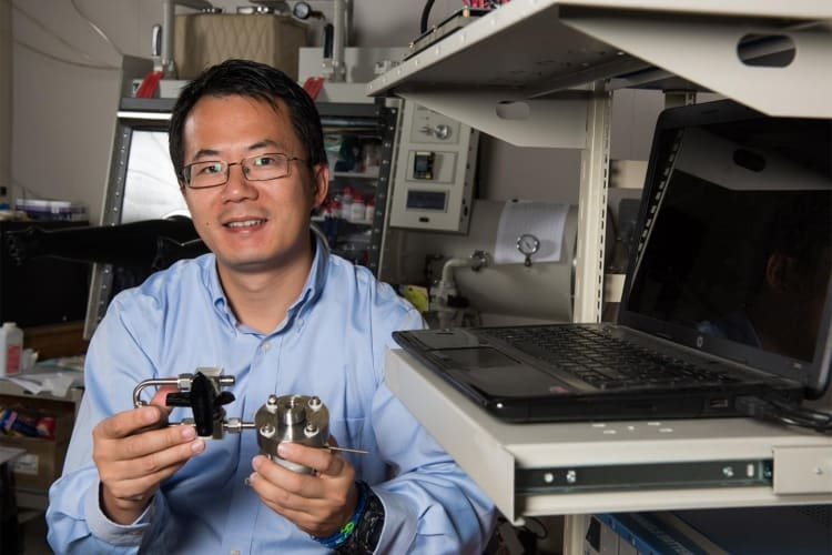 Yiying Wu, professor of chemistry and biochemistry at The Ohio State University, with an early prototype of the solar battery under development in his lab.