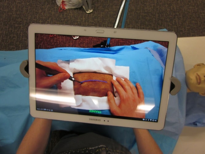 The system uses a transparent display with a tablet positioned between the surgeon and the operating field.