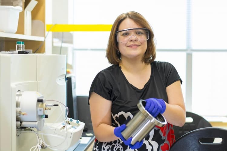 Marion Emmert, assistant professor of chemistry with the drive unit from an all-electric Chevrolet Spark vehicle. She has developed a chemical method for extracting rare earth elements from the unit's magnets.