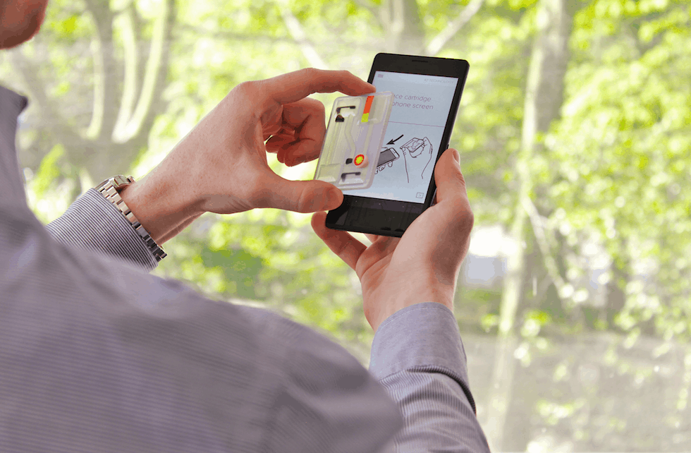 The user adds a sample and positions the transparent test cartridge on the smartphone touchscreen. The phone app then confirms the correct positioning, starts the test and prompts the user to carry out specific actions