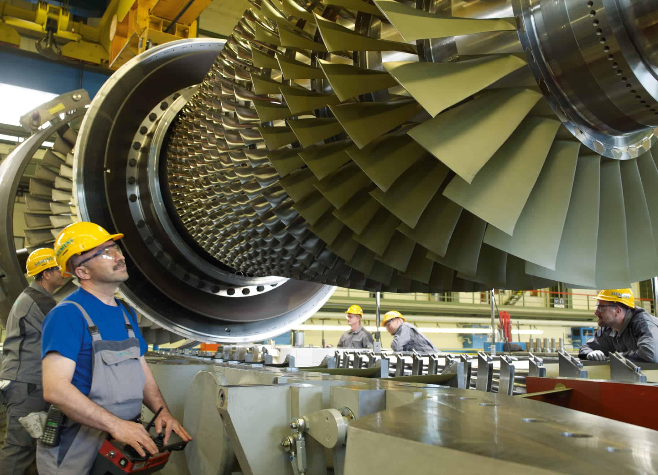 Das Bild zeigt Siemens-Mitarbeiter in der Endmontage beim Einlegen eines Turbinenläufers der Siemens Gasturbine SGT5-4000F. The picture shows Siemens employees in the final assembly hall in the Berlin manufacturing plant while inserting a turbine rotor of the Siemens gas turbine SGT5-4000F.