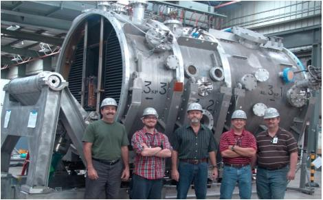 Members of the general Atomics team pose in front of one of the four neutral beam injector housings.